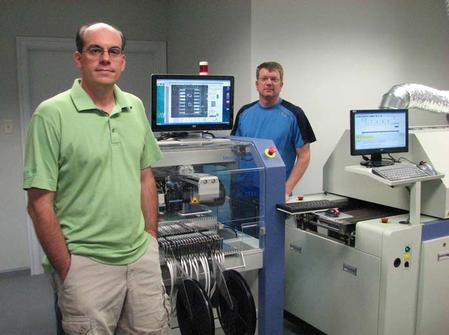 Applied Control & Measurement, LLC, is a former PCB design start-up that now does volume assembly of the very boards it generates. Shown is Brian L. Gery, Owner and Founder (left), and Michael Weil, Director of Operations. They are alongside some of the Manncorp equipment that will achieve targeted production goals -- including the highly flexible MC series pick and place machine and the CR-4000C lead-free reflow oven with KIC Auto Focus Power software.