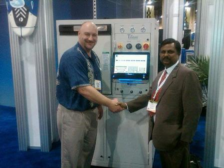 Accurex's Ram Mohann (right) purchases Aqueous Technologies' Trident III from Kevin Buckner (left) during the recently held IPC/APEX Expo in Las Vegas.