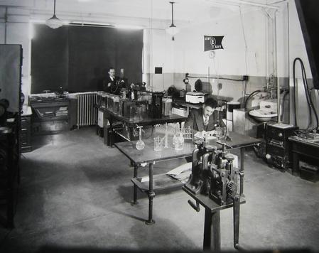 In the early days of Indium Corporation, technologists work in a lab with the U.S. Army/Navy