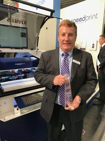Mark Brawley shows off the Global SMT Award on Speedprint's booth at Productronica.
