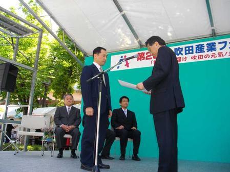 Shigehiro Teranishi, President of the fair, presents a Suita Industry Award to Tetsuro Nishimura, President of Nihon Superior Co. Ltd.