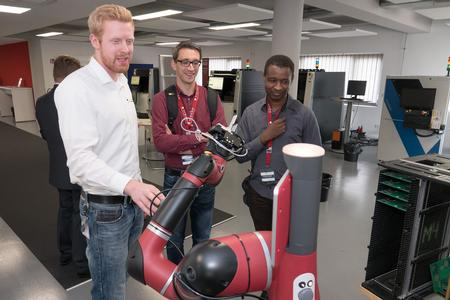 Georg Walz, who is writing an undergraduate thesis at Viscom, shows Sawyer working at an inspection system to guests at the Viscom Technology Forum 2018 in Hanover, Germany.