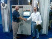 Aqueous Technologies Corp.'s Kevin Buckner (left) sold a Trident III to Bob Kajfasz of Advance Circuit Technology (right) during the recently held IPC/APEX Expo in Las Vegas.