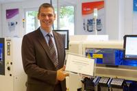 Jens Mirau, President of Juki Automation Systems GmbH, shows the Outstanding Performance Award.