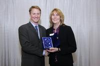 DEK's Global Marcom Director, Karen Moore-Watts, accepts the NPI Award from Circuits Assembly's Mike Buetow